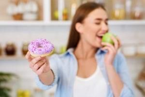 Girl holding donut but eating apple