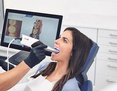 Photo of a brunette woman sitting in a dental chair and having her teeth scanned with a CEREC handheld digital camera.