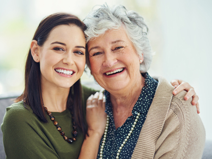 Photo of a young brunette woman with her arm around a gray-haired senior woman; for information on natural-looking dentures in Monroe, LA.