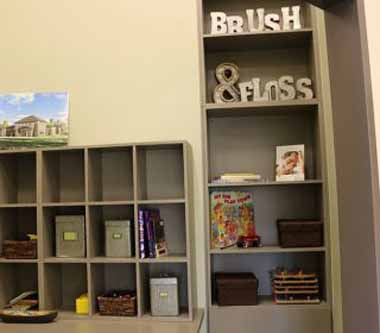 Books and toys shelves photo in the reception area of Bayou Dental Group in Monroe, LA, the office of Dr. David Finley and Dr. P.J. Henderson.