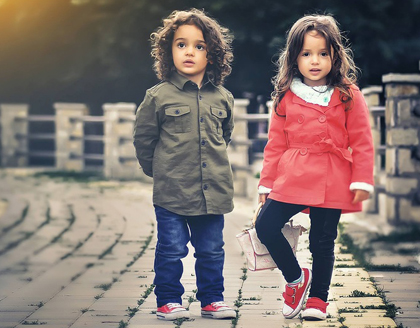 Photo of a preschool boy and girl with brunette hair standing on a brick walking bridge; for information on Monroe, LA pediatric dentistry from David Finley and PJ Henderson.