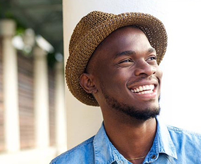 Head-and-shoulders photo of a black man wearing a tan woven hat and smiling; for information on sedation dentistry in Monroe, LA.