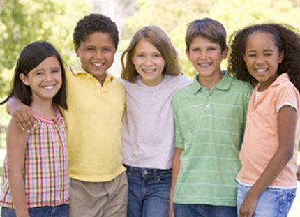 Photo of five children, two boys and three girls, standing outdoors and smiling; for information on children's dentistry in Monroe, LA.