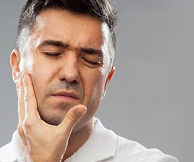 Photo of a dark haired man holding the right-hand side of his face; for information on having a hard time chewing, from Bayou Dental Group in Monroe, LA.