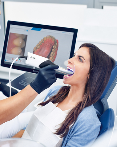 Photo of same-day crown technology and a brunette woman sitting in a dental chair as her teeth are being scanned.