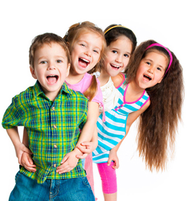 Photo of four kids (a boy with three girls behind him) standing and smiling; for information on pediatric dentisty.
