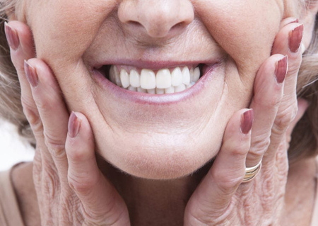 Nose-to-chin photo of a senior woman smiling and holding her face, for information on cosmetic dentures from Monroe, LA dentist Dr. David Finley.