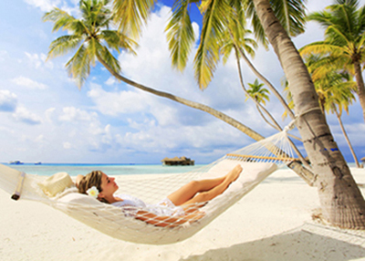 A young woman lying in a hammock that is tied to palm trees alongside the ocean; for information on how relaxing sedation dentistry should be.